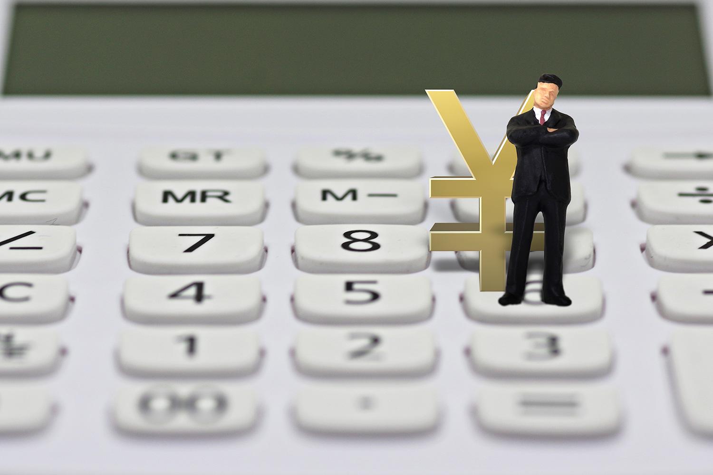 電卓の上でお金について悩むサラリーマンの人形